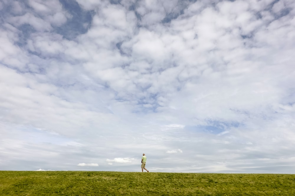 person standing on green grass field under white clouds and blue sky during daytime