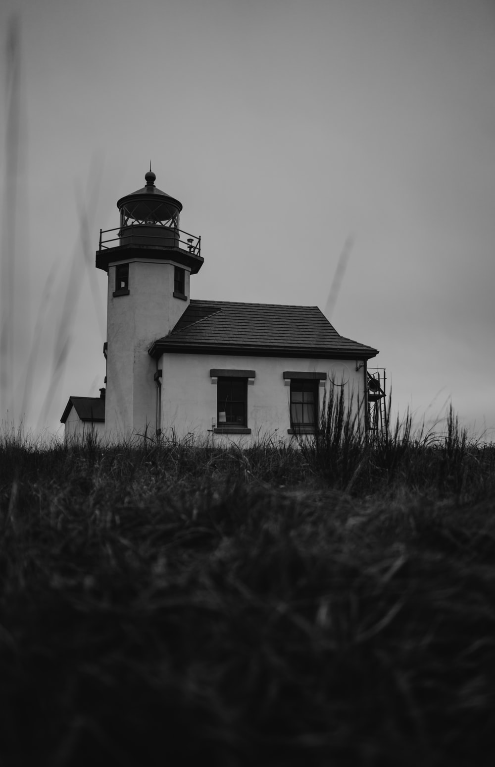 grayscale photo of lighthouse near grass field