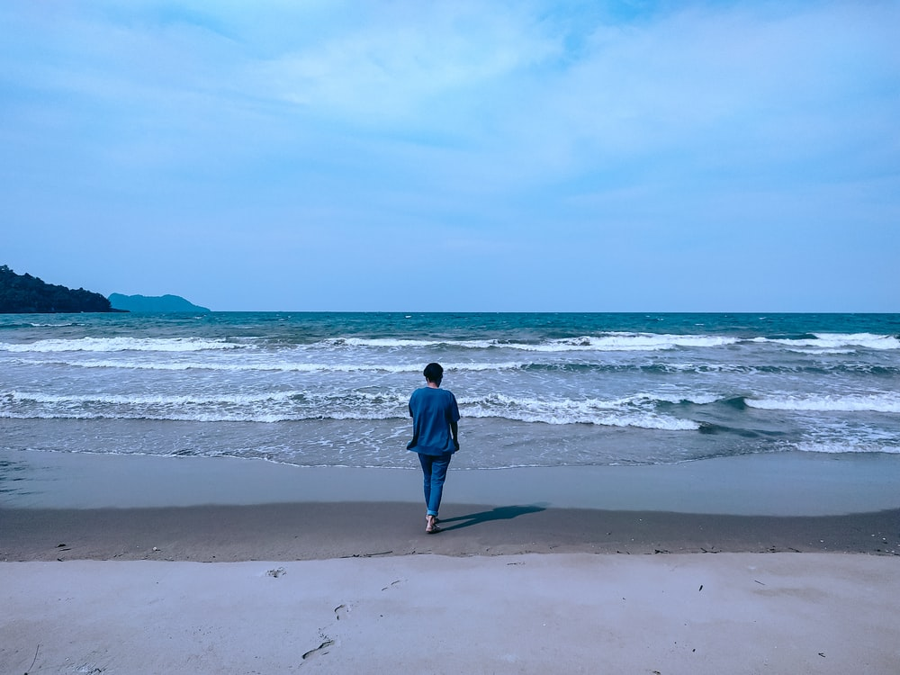 woman in blue jacket walking on beach during daytime
