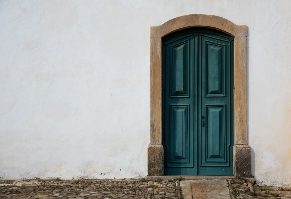 blue wooden door on white concrete wall