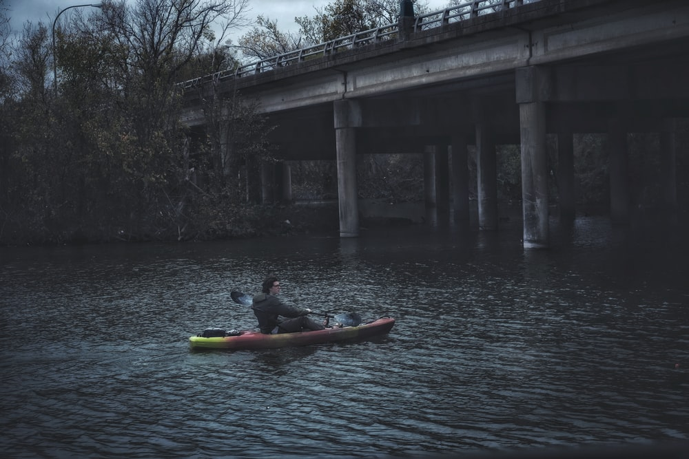 man in red kayak on river during daytime