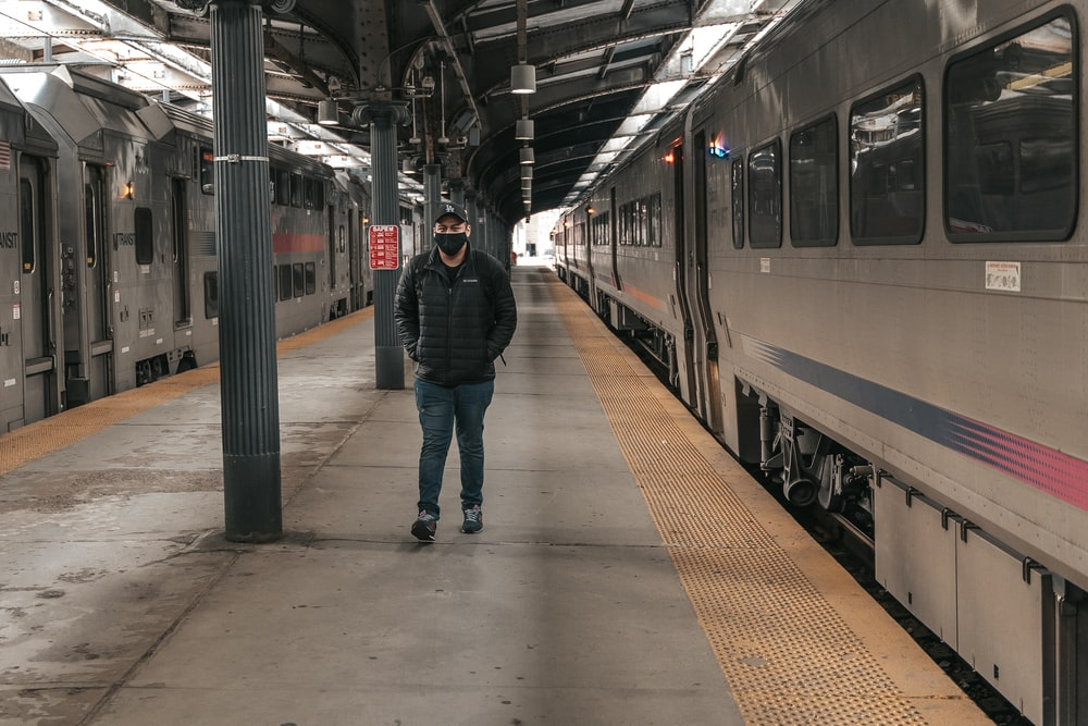 man in black jacket and blue denim jeans standing on train station