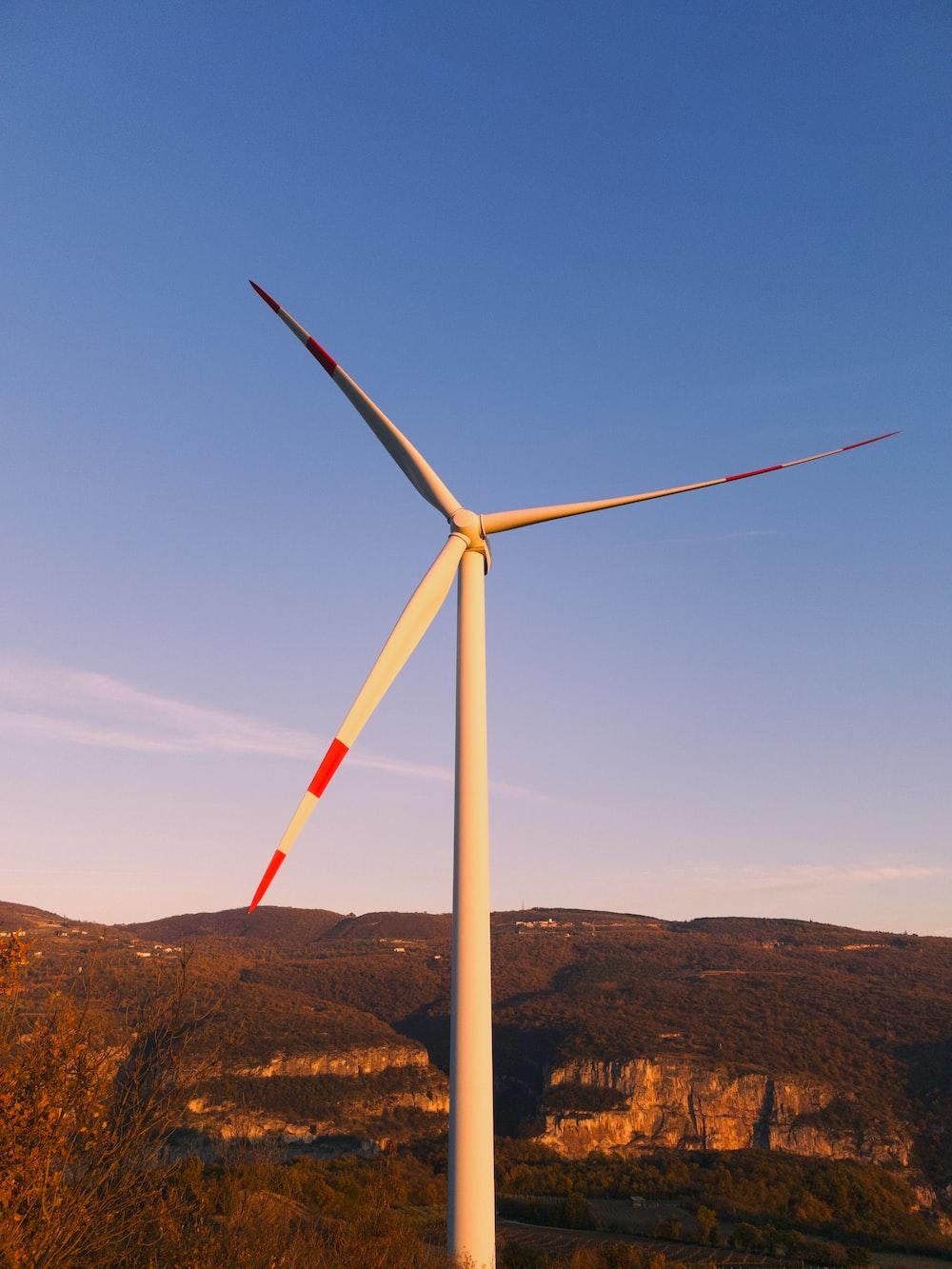 white wind turbine on brown field under blue sky during daytime