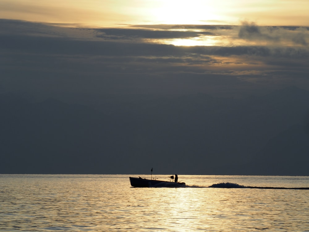silhouette of person riding on boat on sea during sunset