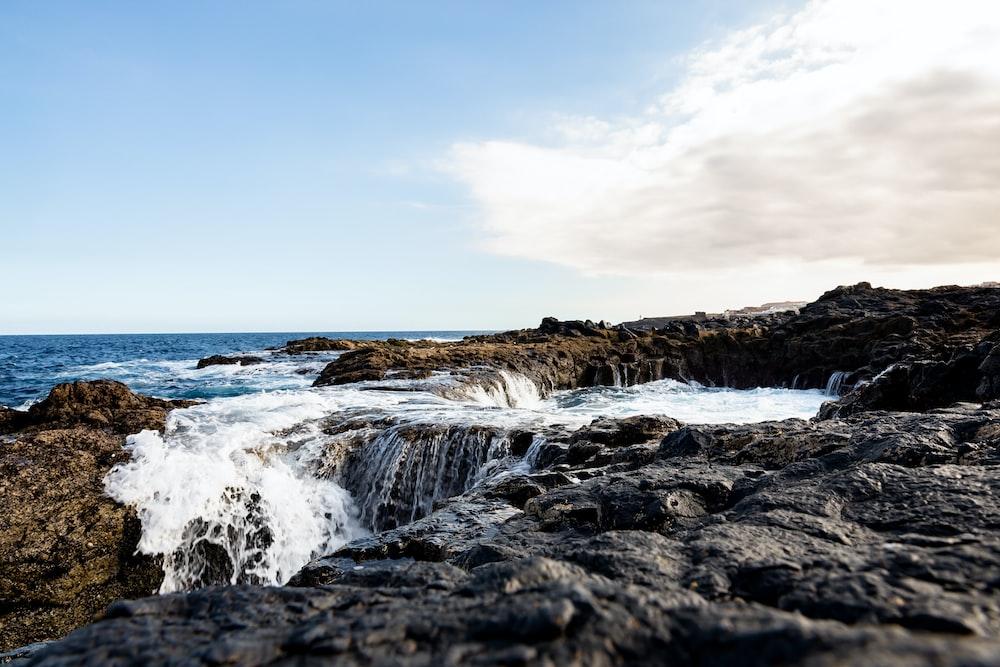 ocean waves crashing on rocks under blue sky during daytime