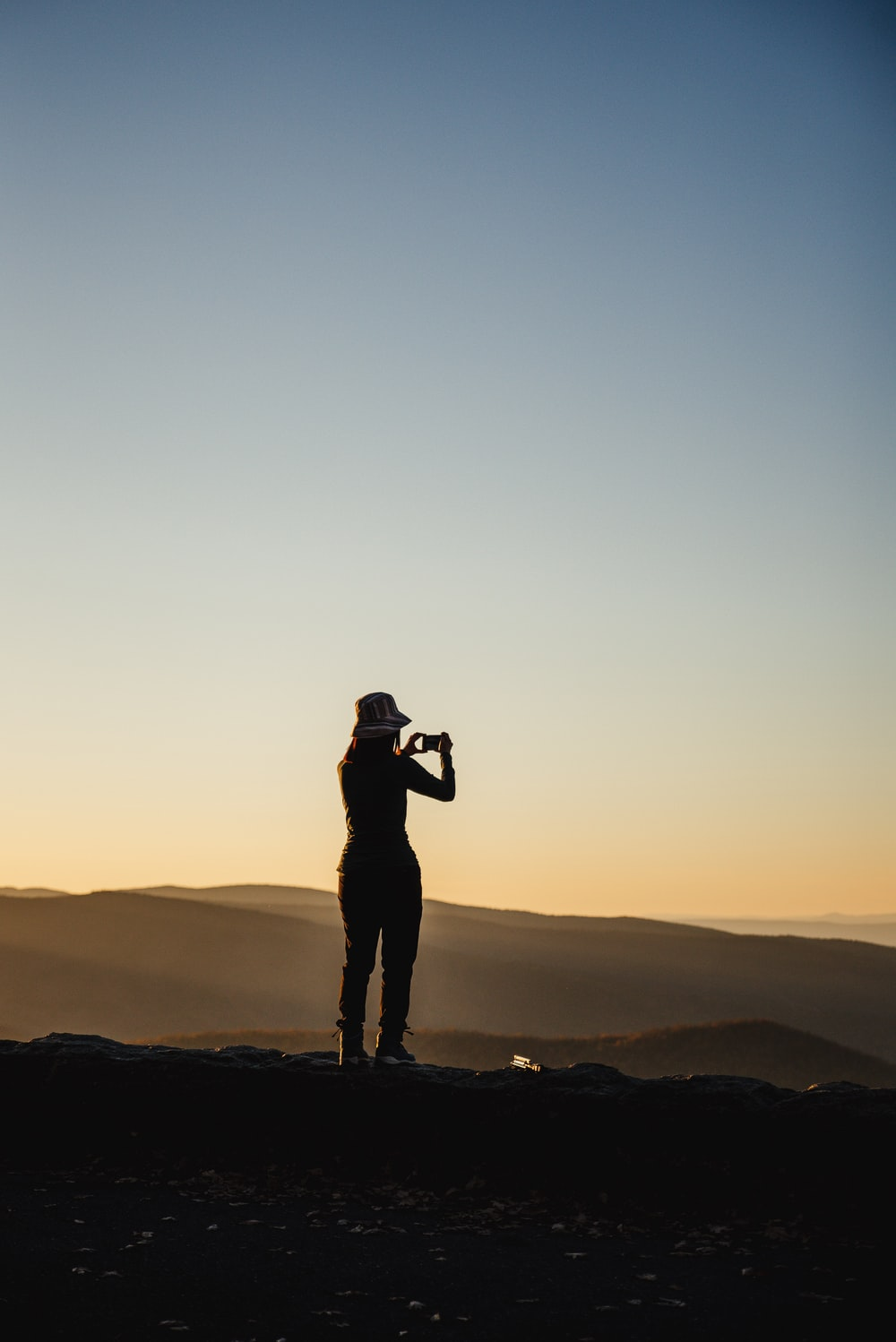 silhouette of man standing on top of mountain during sunset