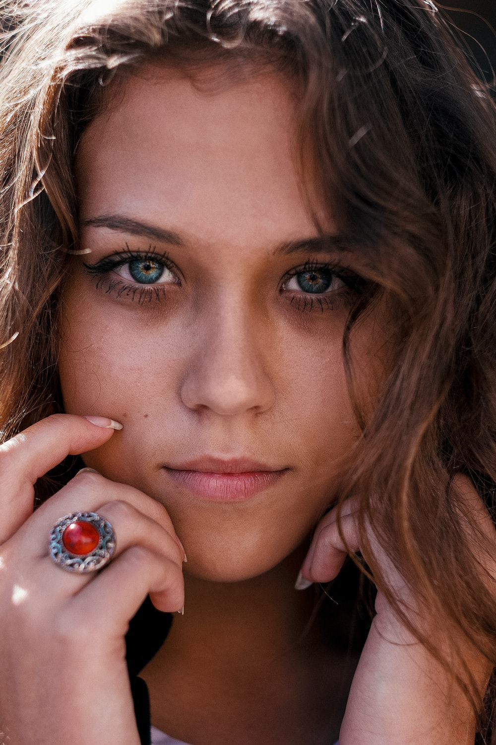 woman with brown hair and wearing silver ring