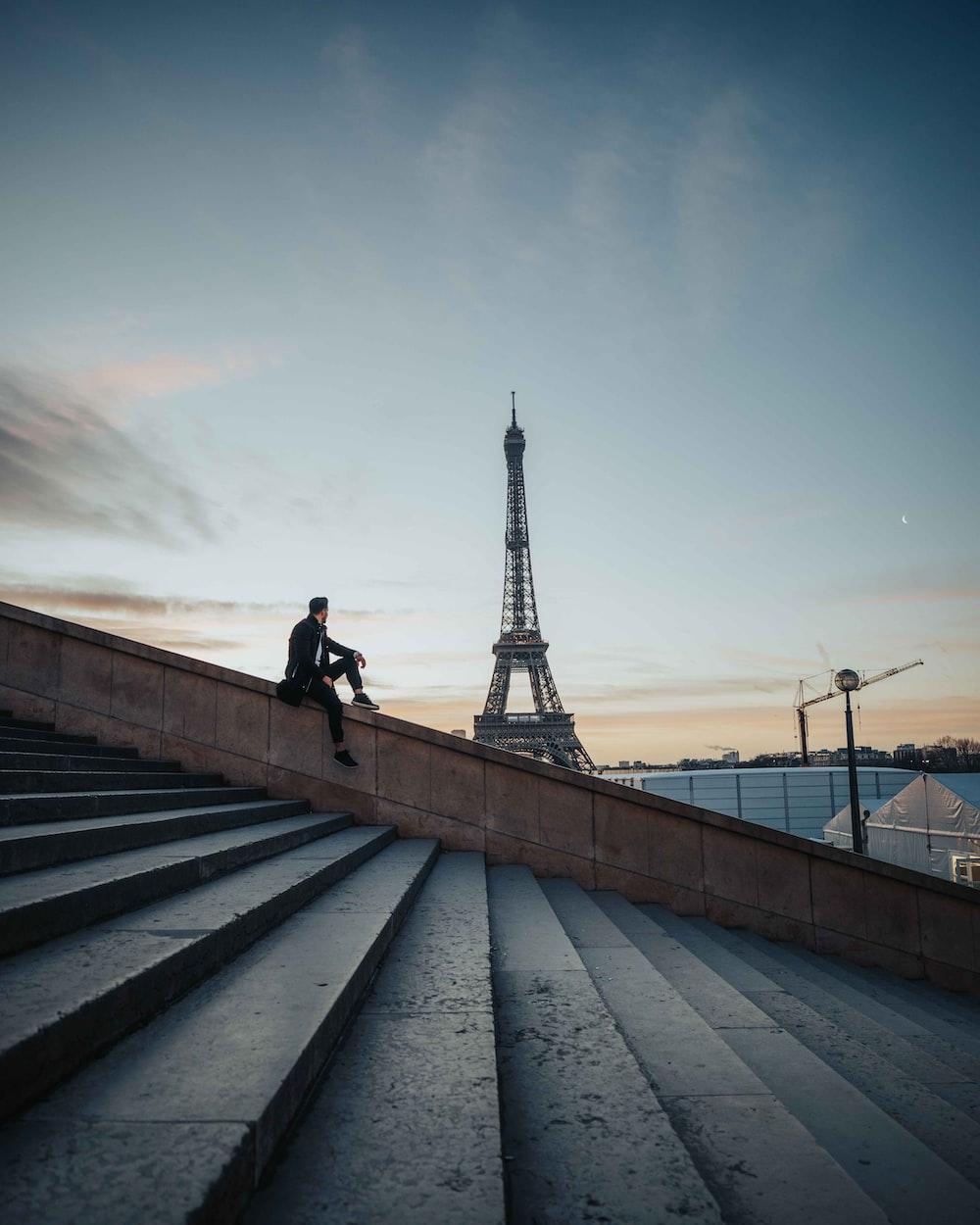 man in black jacket walking on gray concrete bridge during daytime