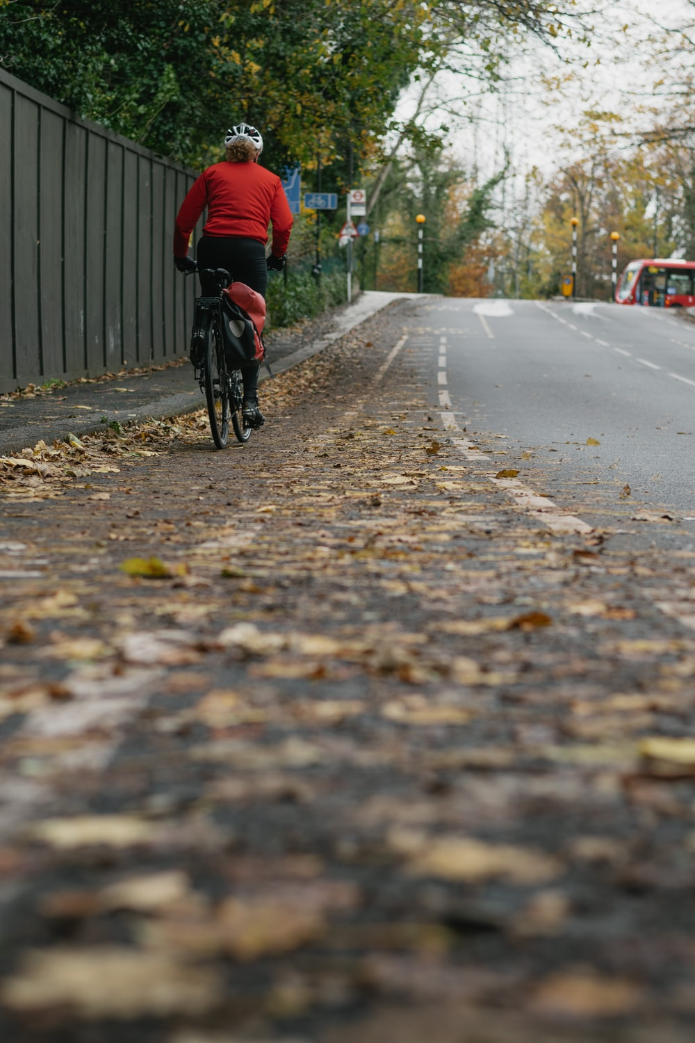 man in red jacket riding bicycle on road during daytime