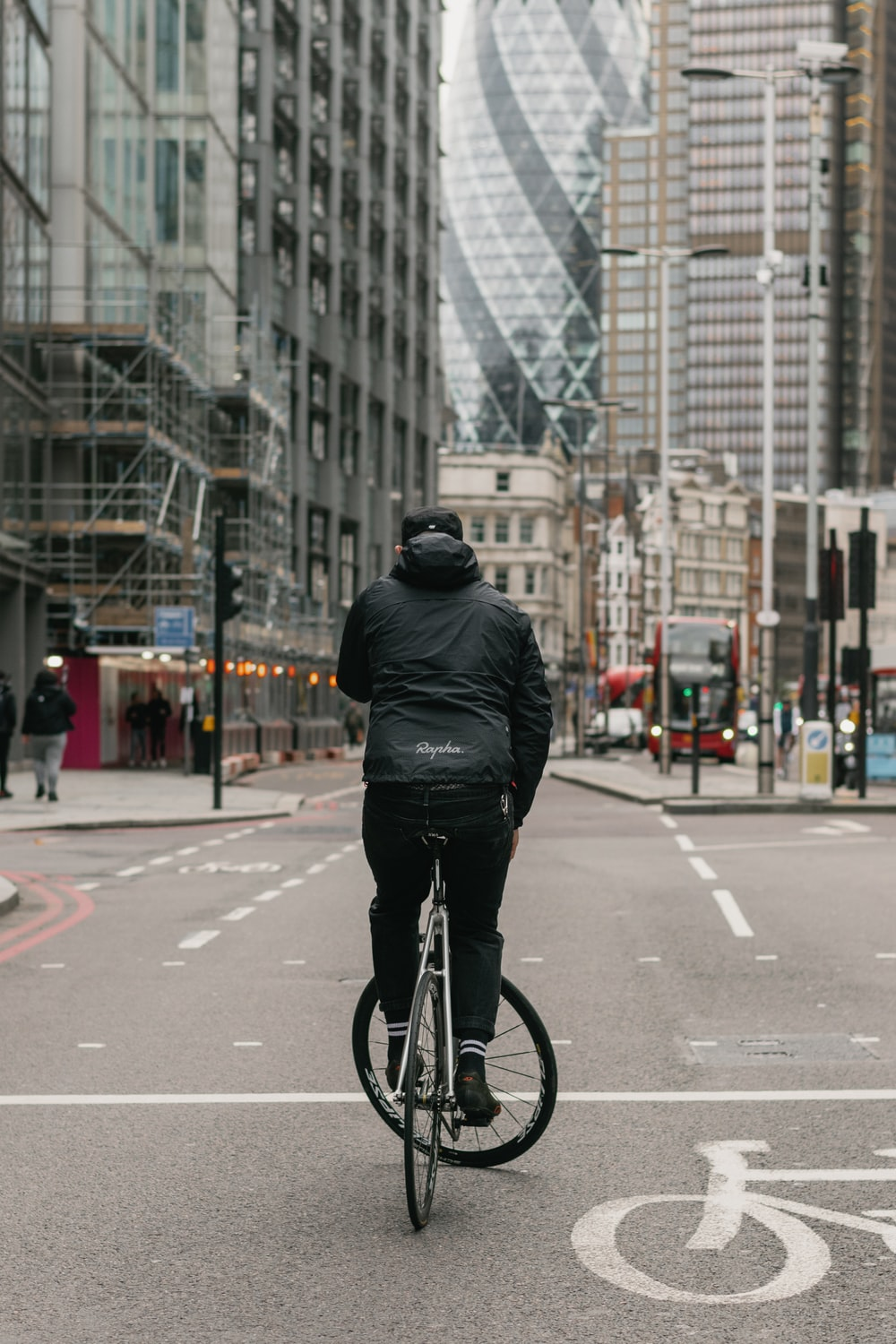 man in black leather jacket riding bicycle on road during daytime