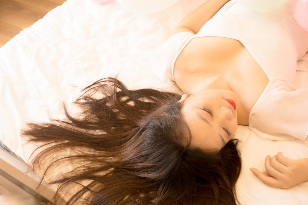 woman in white brassiere lying on white bed