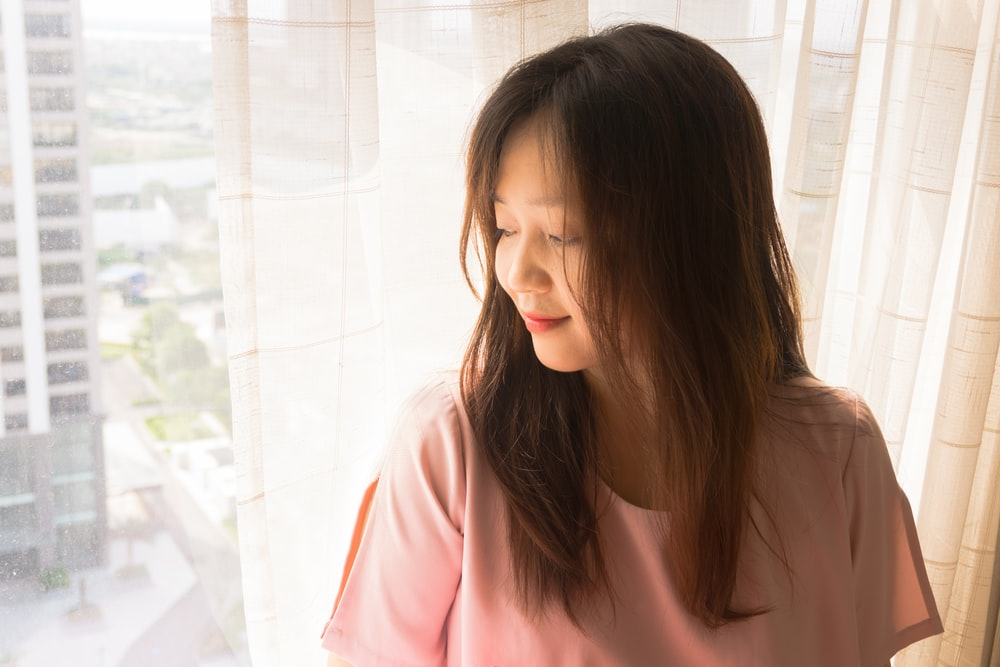 woman in pink shirt standing near white tiled wall