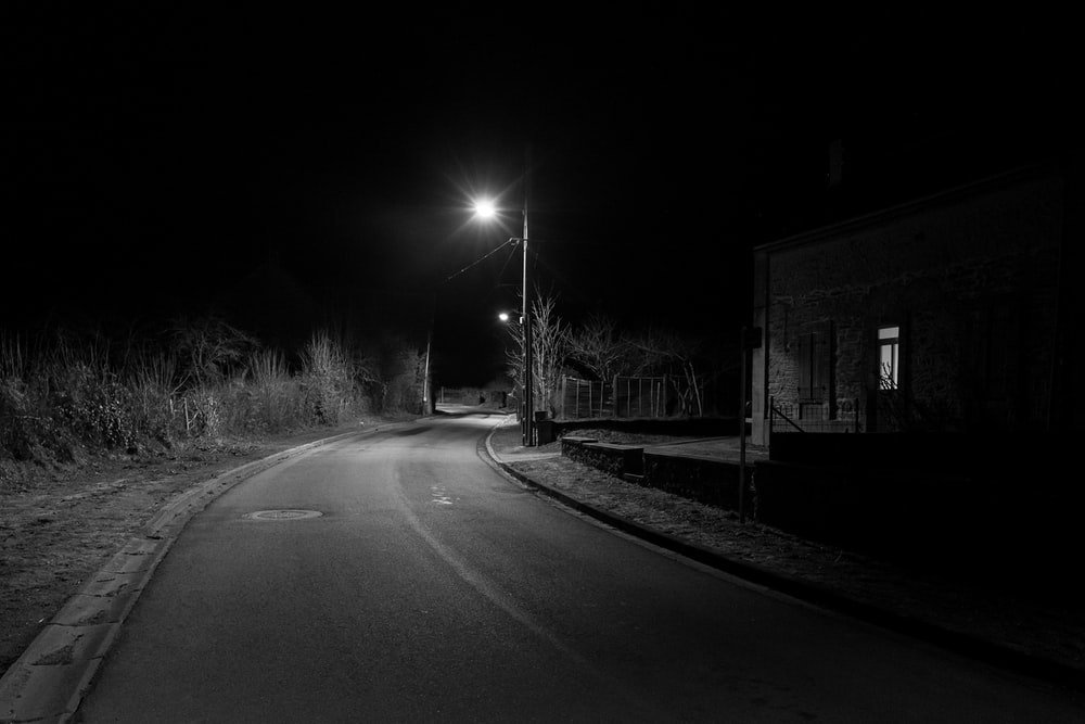 grayscale photo of road with street lights