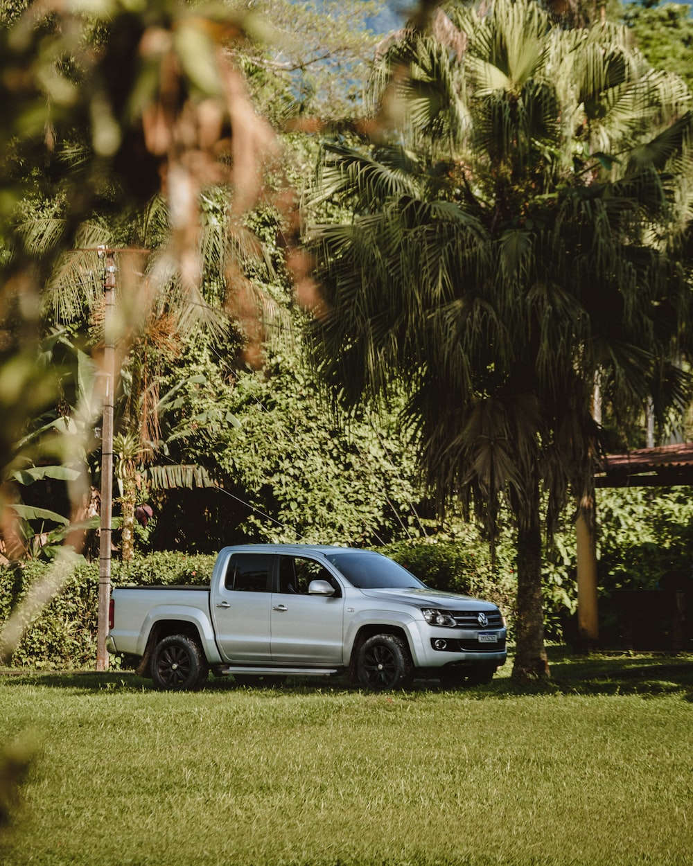 white and blue chevrolet crew cab pickup truck parked on green grass field during daytime