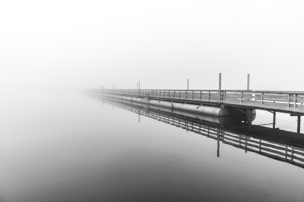 grayscale photo of bridge over body of water