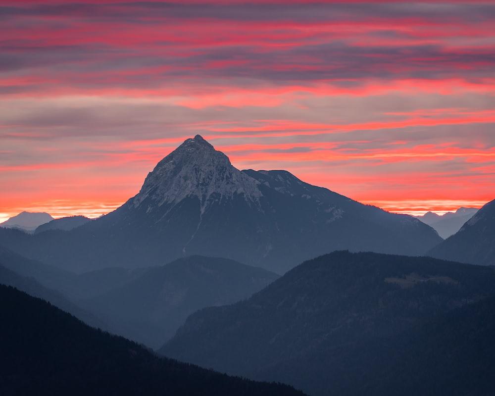 black and white mountains under orange sky