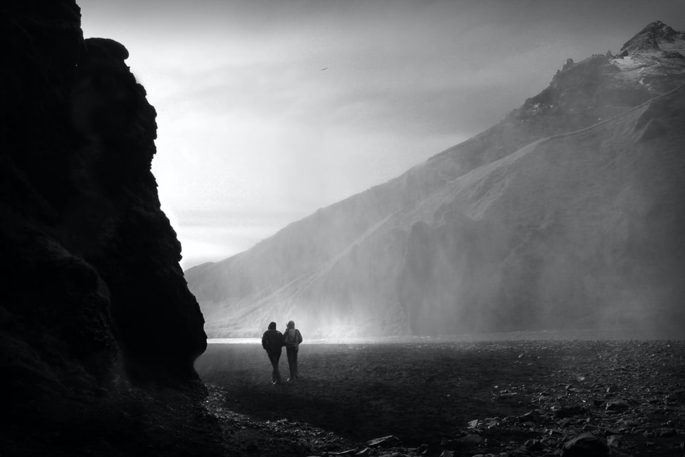 2 person standing on rock formation near mountain during daytime