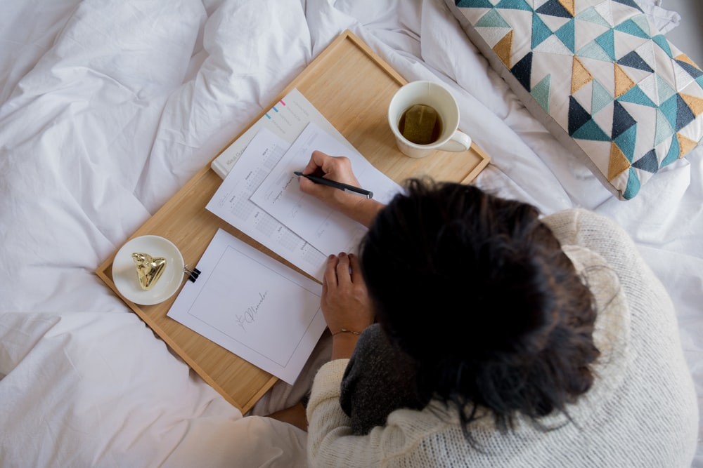 person writing on white paper beside white ceramic mug on white textile
