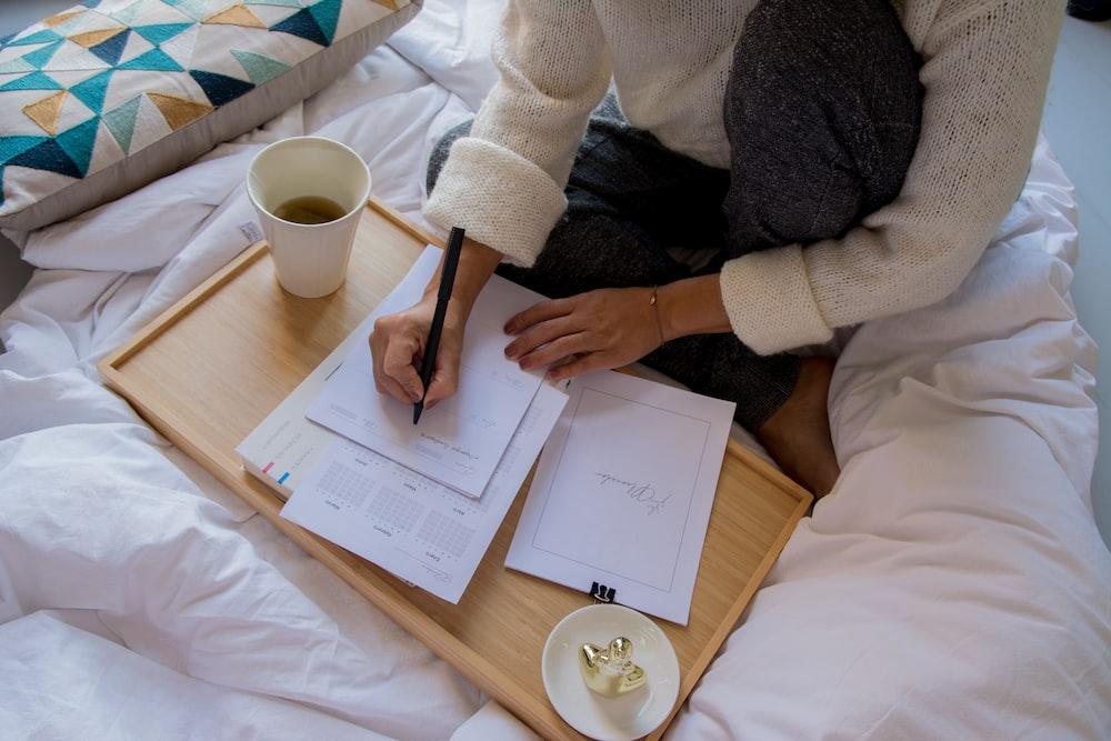 Kahverengi ahşap masada beyaz seramik kupa yanında beyaz kağıda yazı yazan beyaz kazaklı kişi