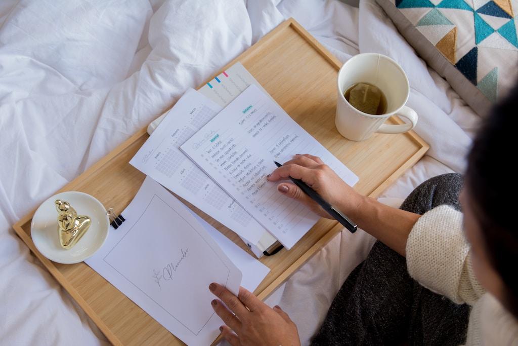 person holding white printer paper near white ceramic mug on white textile