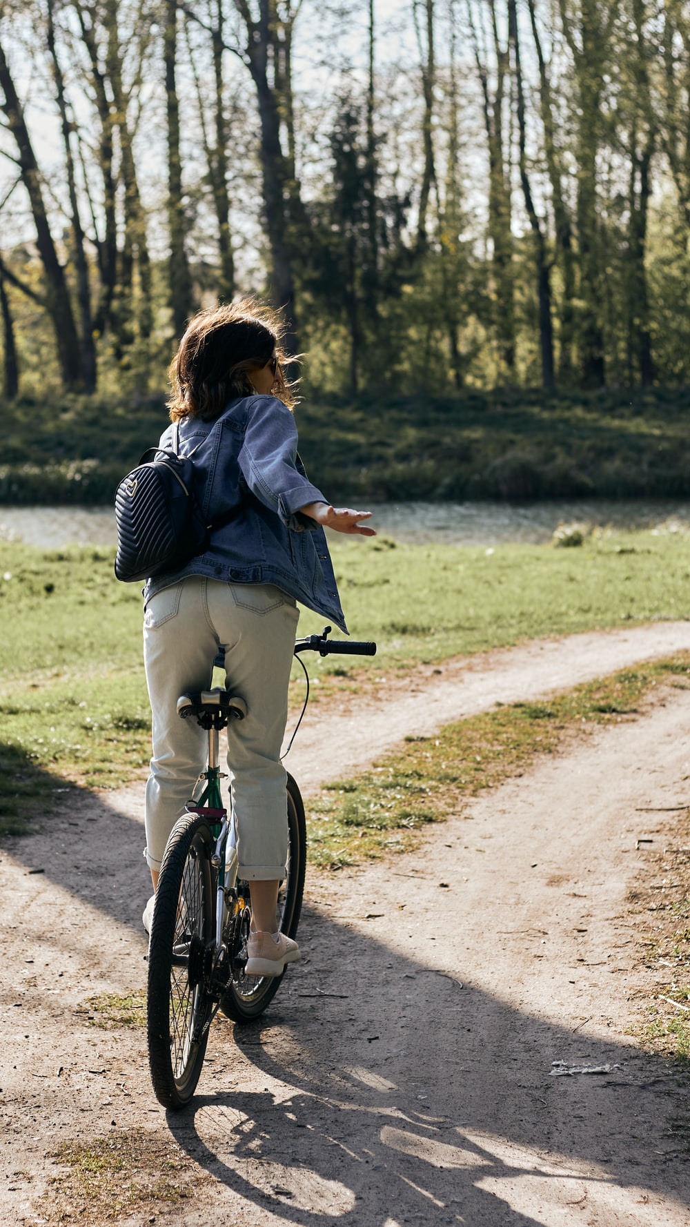 woman in black and white stripe long sleeve shirt riding on bicycle on road during daytime