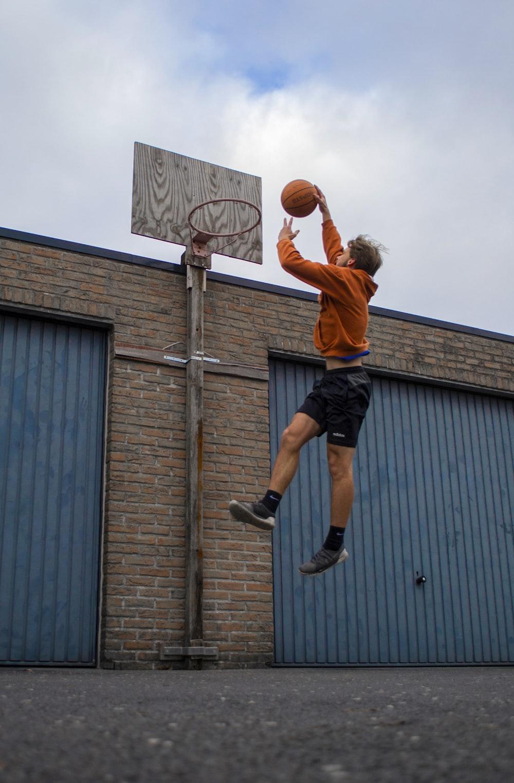 man in orange shirt and black shorts playing basketball