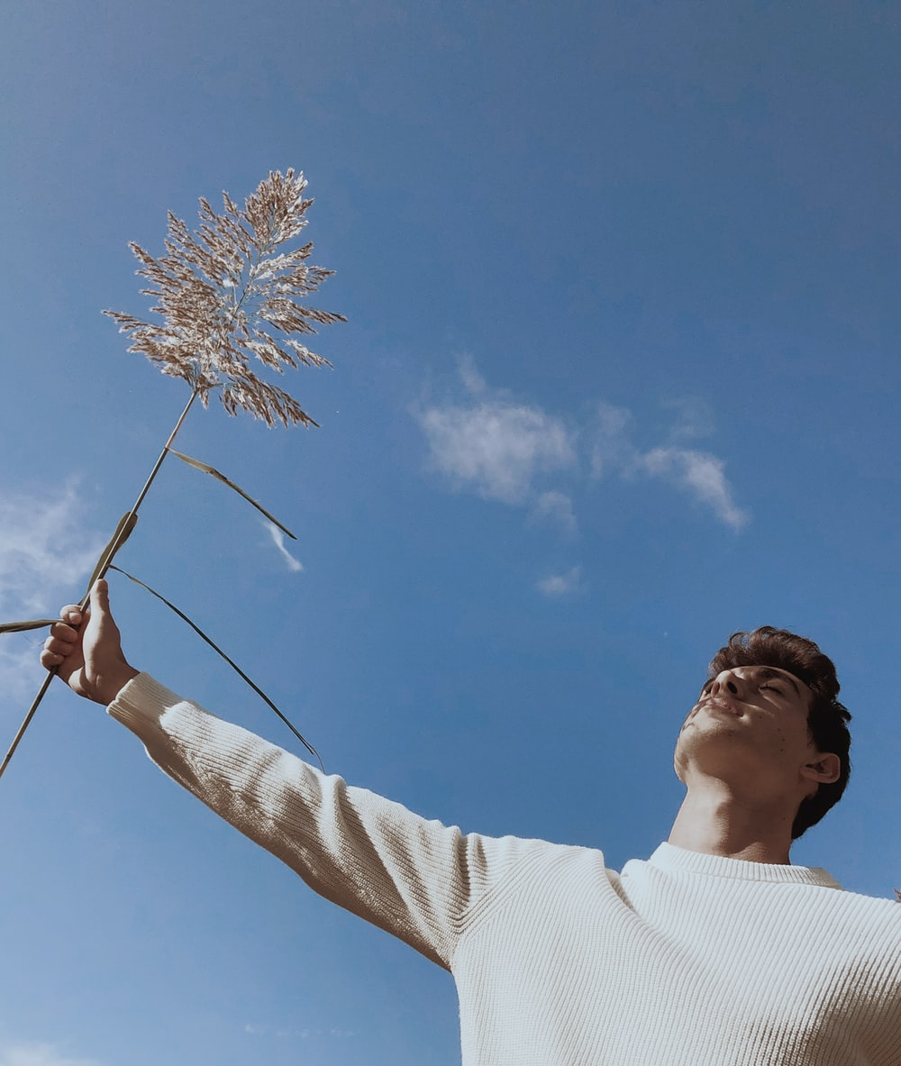 man in white sweater holding brown and white flower under blue sky during daytime