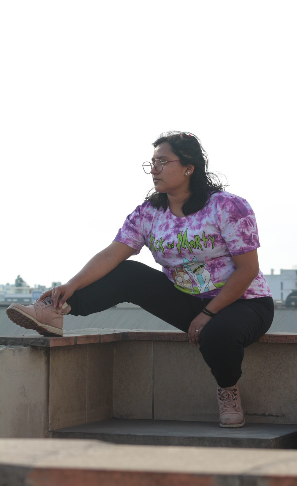 woman in purple and white floral shirt and black pants sitting on concrete bench during daytime