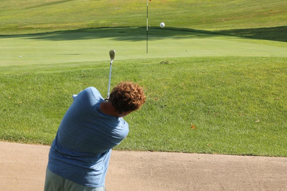 man in gray shirt playing golf during daytime
