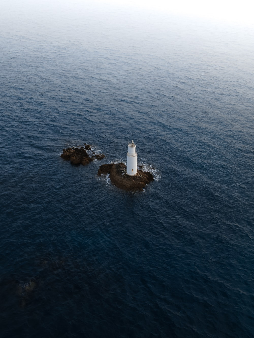 white and brown lighthouse on brown rock formation in the middle of sea during daytime