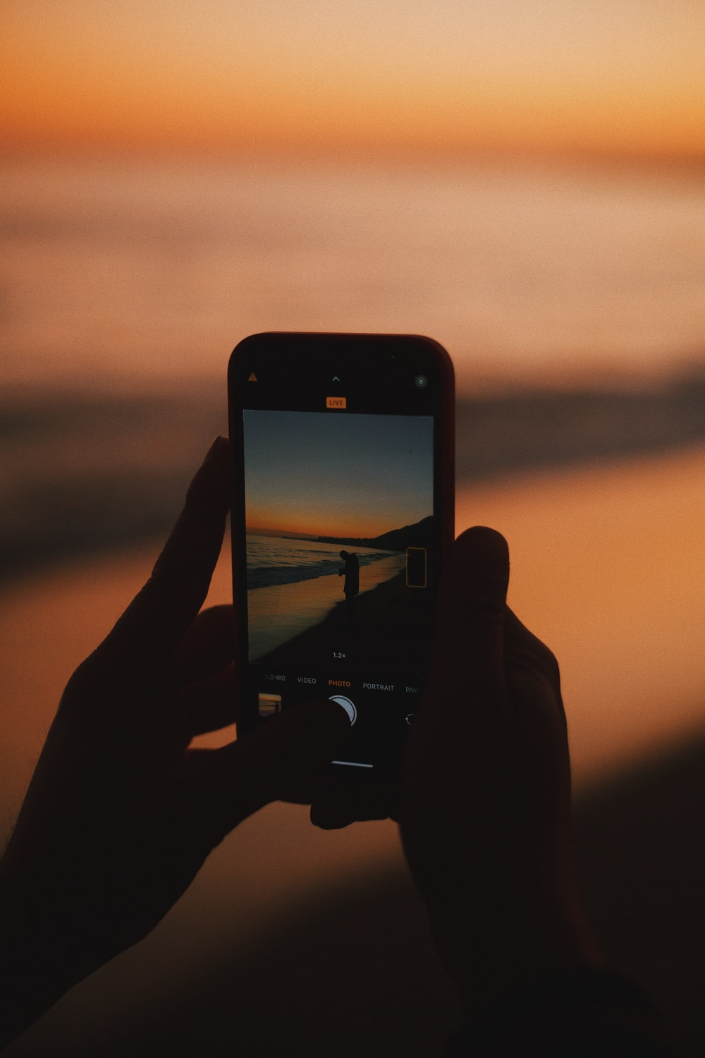 person holding iphone taking photo of sunset
