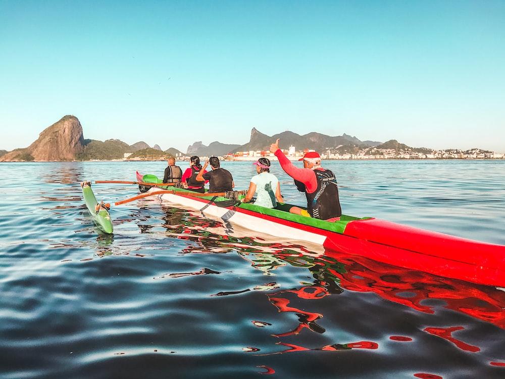people riding red kayak on sea during daytime