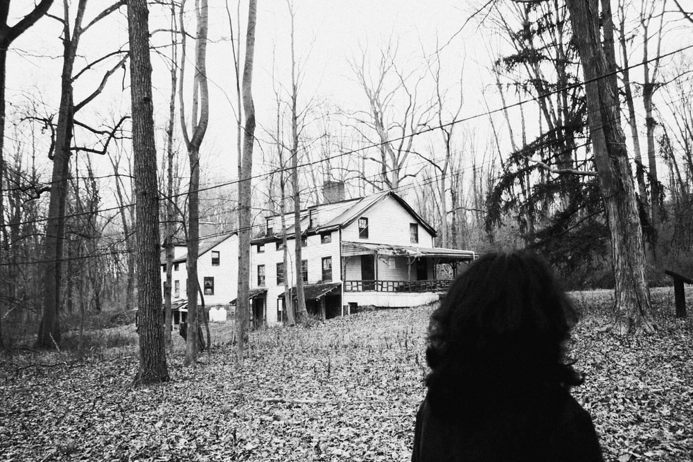 grayscale photo of woman in black coat standing near bare trees