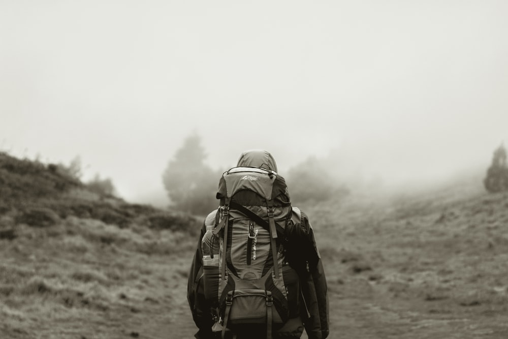 grayscale photo of man in backpack walking on dirt road