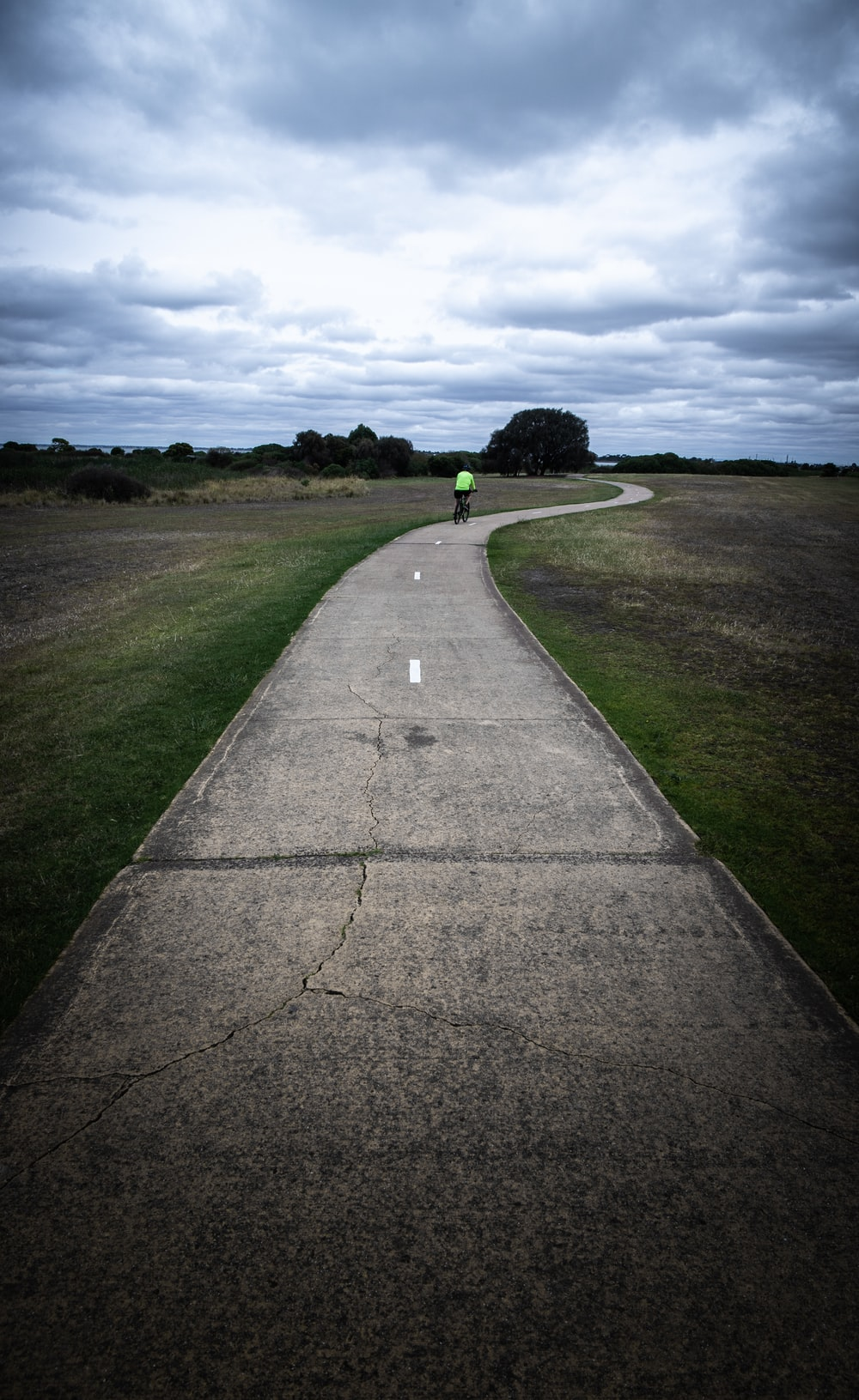 gray concrete road between green grass field under gray clouds during daytime