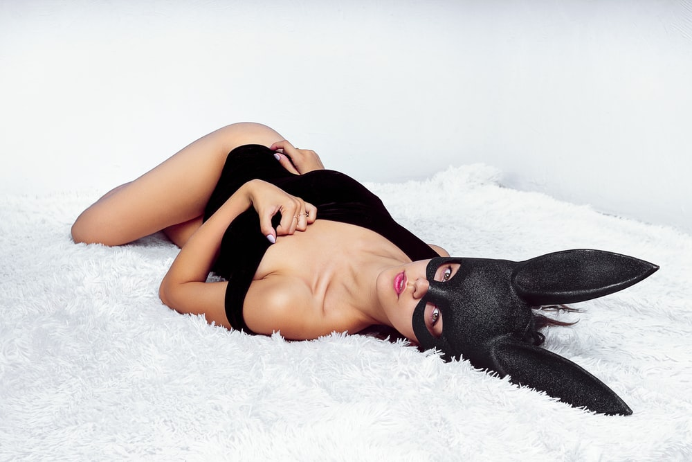 woman in black brassiere lying on white textile