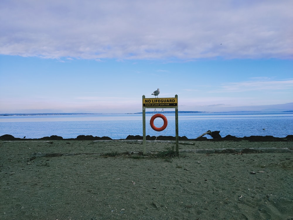 white and yellow road sign near sea under blue sky during daytime