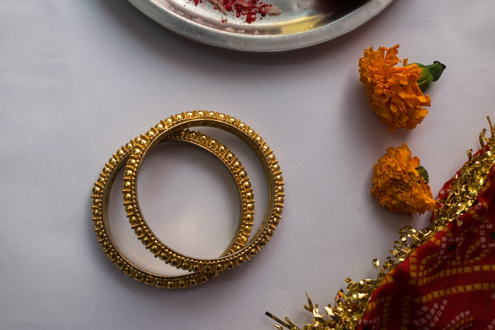 gold and silver bracelet on white table