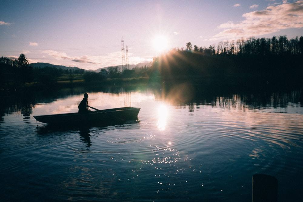 silhouette of person riding canoe on calm water during sunset