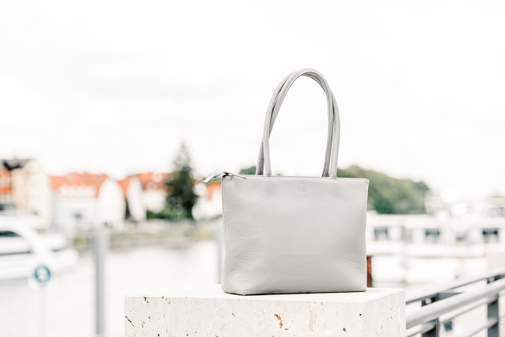 white and brown tote bag on white wooden table