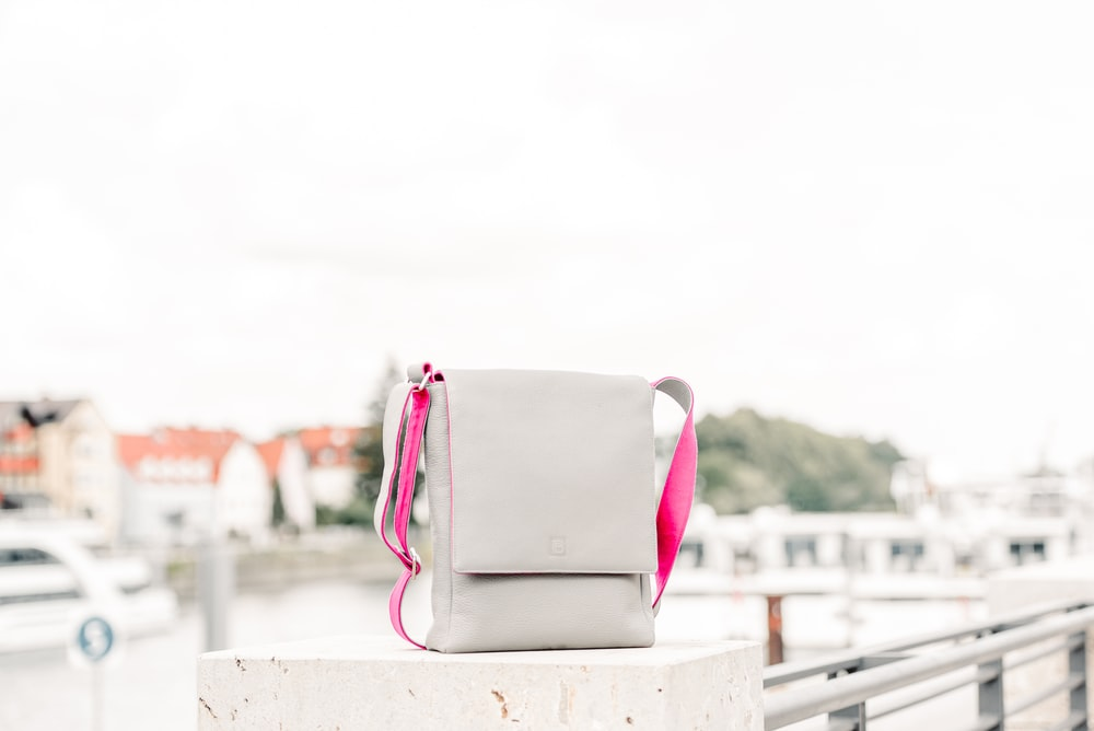 pink and white handbag on white wooden fence