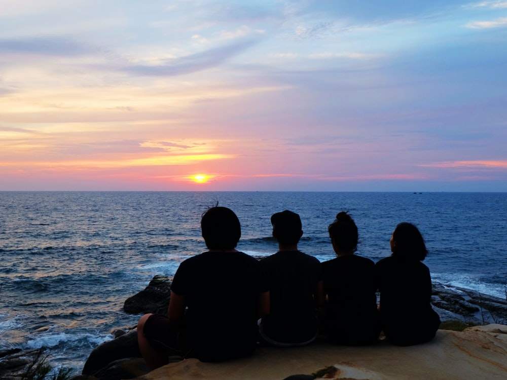 silhouette of people sitting on seashore during sunset