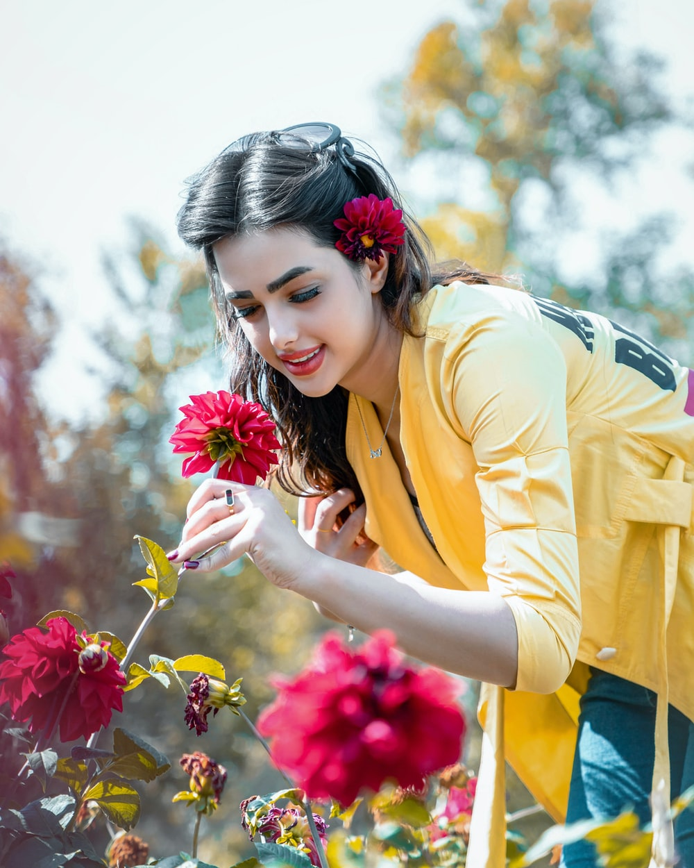 woman in yellow cardigan holding pink flower during daytime