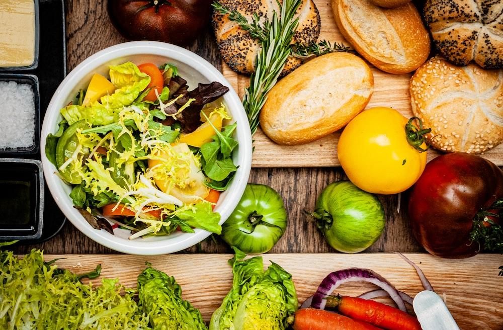 vegetable salad on white ceramic bowl beside bread and sliced bread