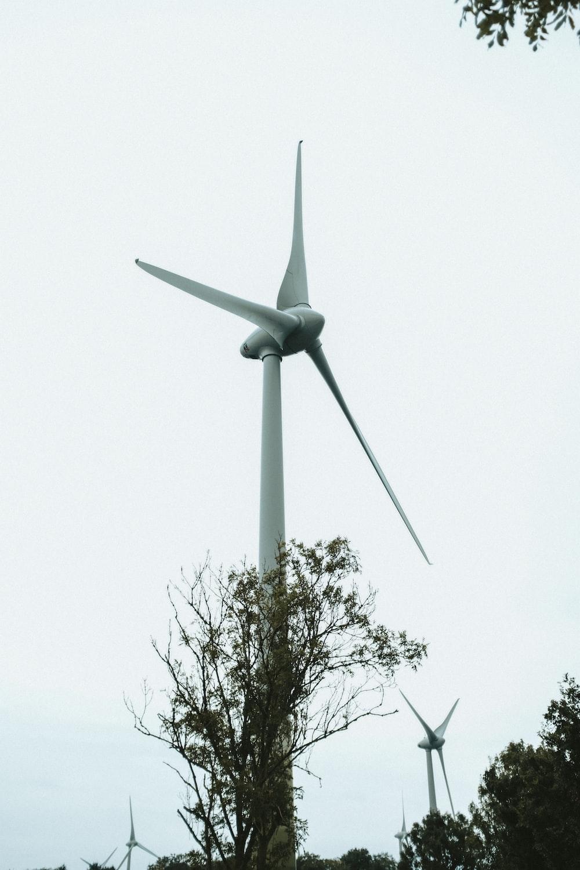white wind turbine under white sky during daytime
