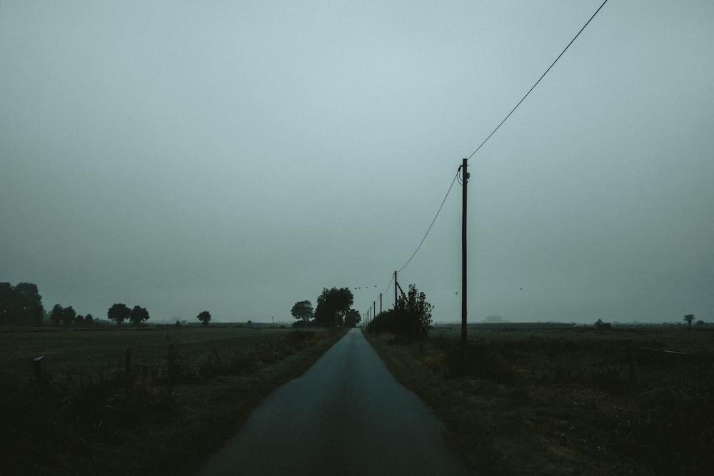 gray road between green grass field under gray sky