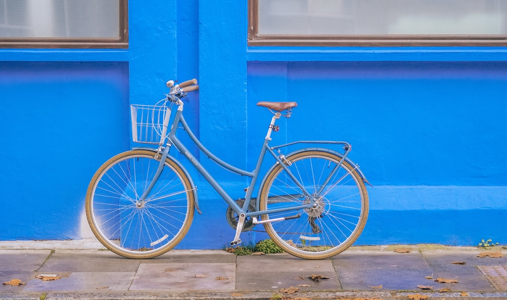 blue city bike parked beside blue painted wall