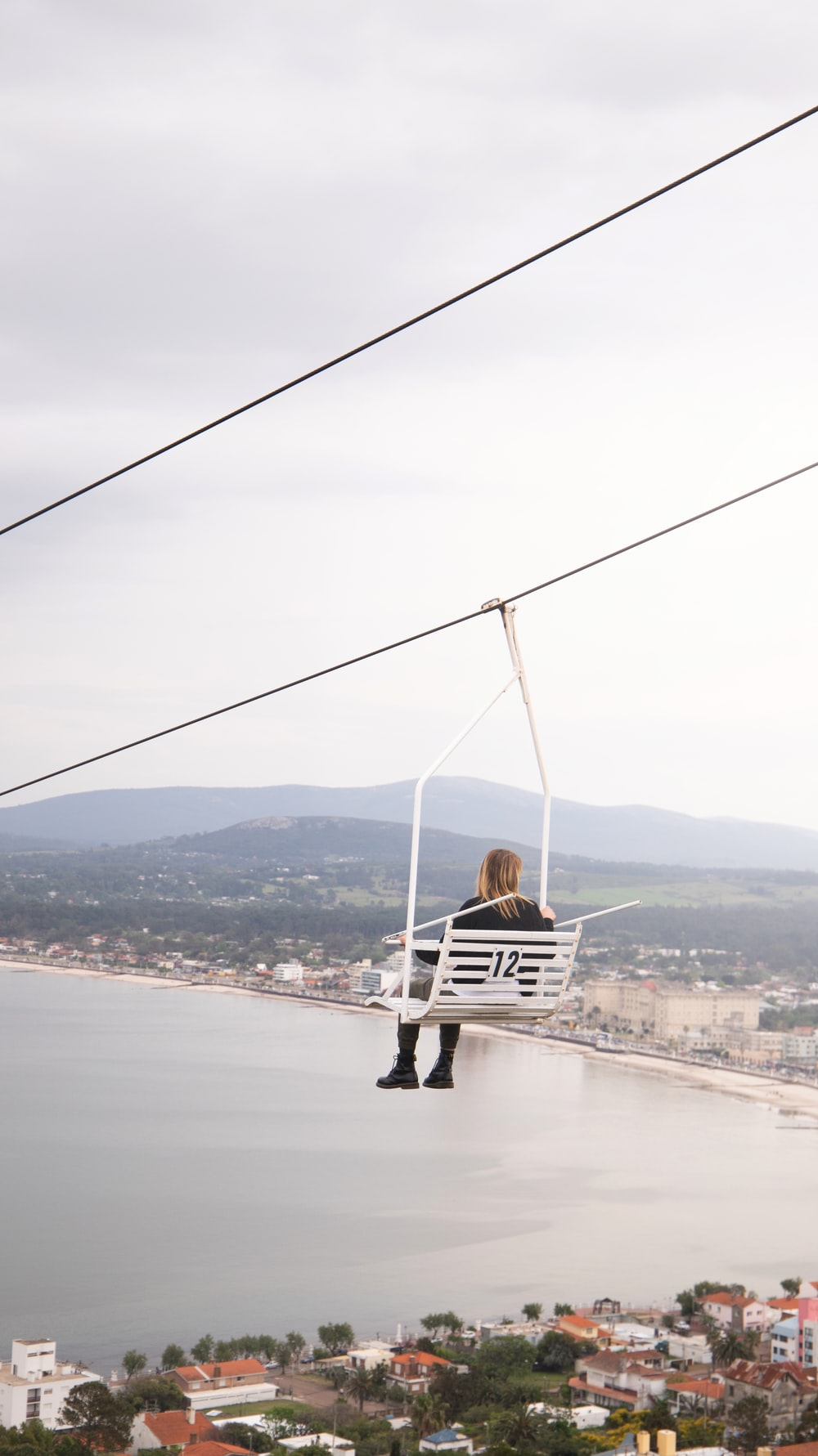 woman in black and white striped shirt sitting on white and black swing during daytime
