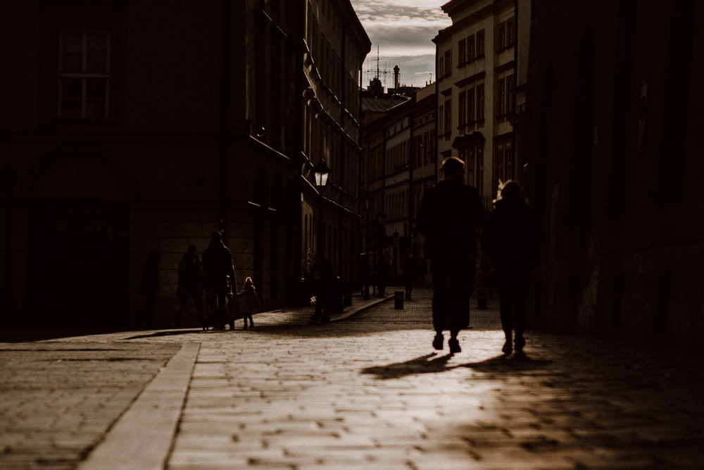 silhouette of man and woman walking on street during daytime