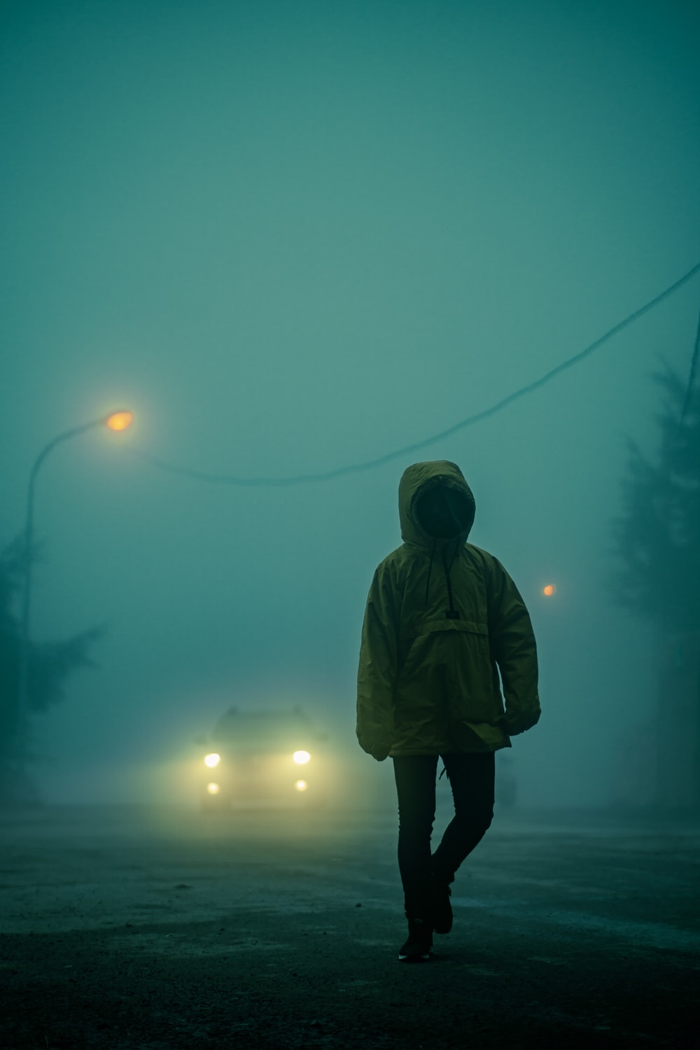 person in brown hoodie standing on road during night time